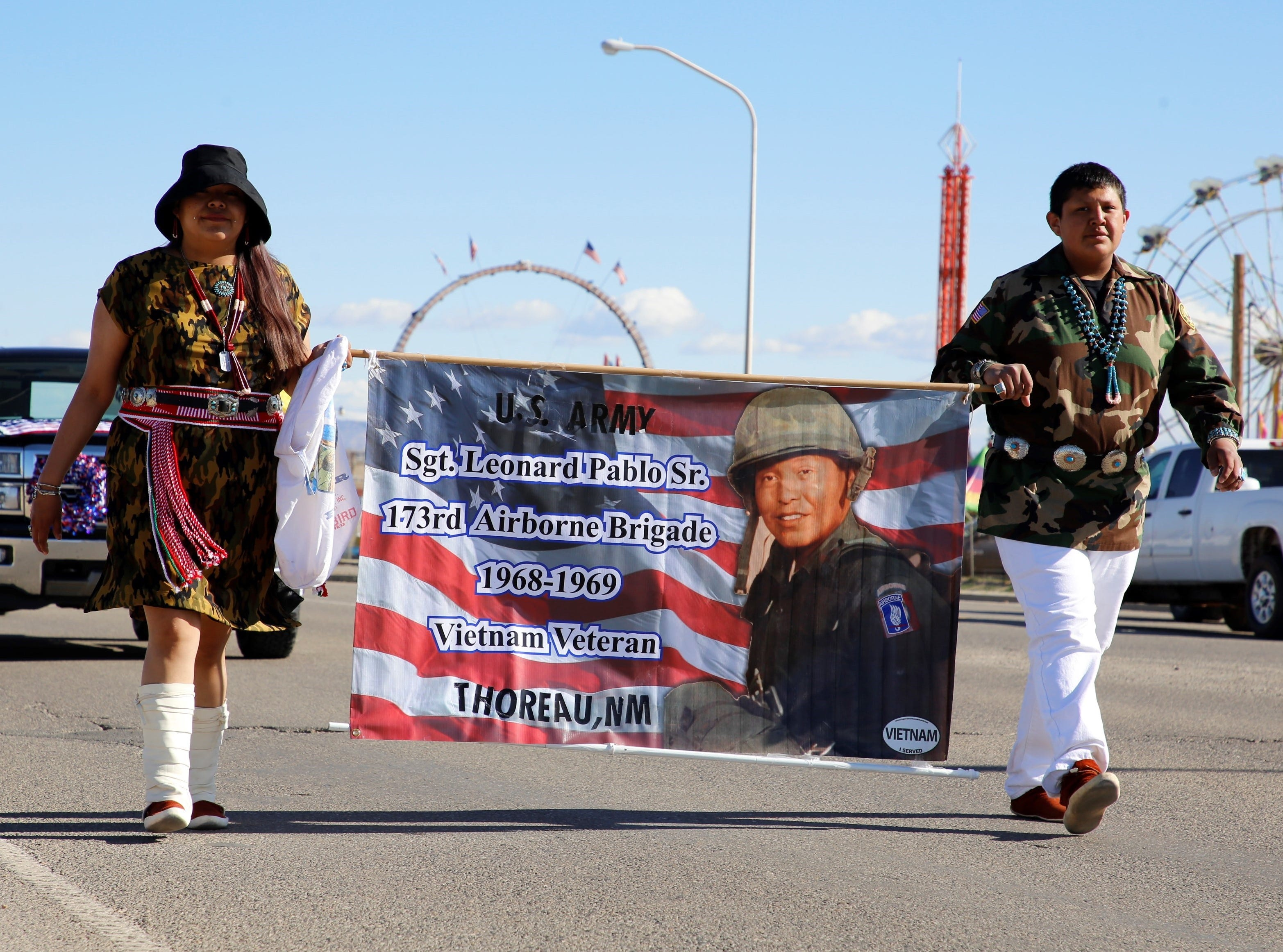 From left, Thoreau residents Lynette Pablo and Elijah Pablo carry a banner on Friday that honors Army Sgt. Leonard Pablo Sr., who served in the Vietnam War.