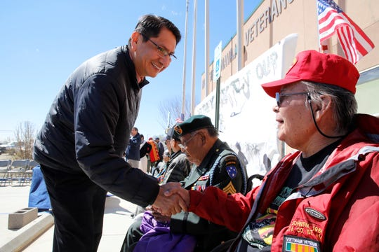 Navajo Nation President Jonathan Nez shakes hands with Vietnam War veteran Morris Johnson, who is one of four Purple Heart recipients named grand marshal of the Vietnam Veterans Day parade in Shiprock on Friday.