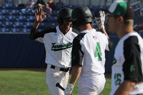 Farmington's Vegas Vondra welcomes Jacob Darwin (8) back to the dugout after Darwin beats the throw to home plate for a run against Rangeview, Colorado during Thursday's game at Ricketts Park.