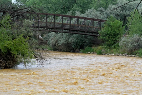 Water from the Gold King Mine spill is seen flowing down the Animas River, Saturday, Aug. 8, 2015, at Berg Park in Farmington.
