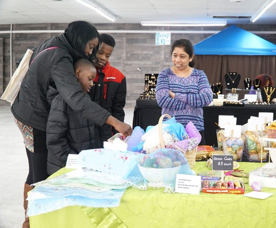 Shirin Bhindarwala chats with Canton resident Cheri McKentry, left, and her kids Jaden, 7, and Jaqub, 10, as they check out her Rose Best goods at the Westland Mini Mall on March 29.