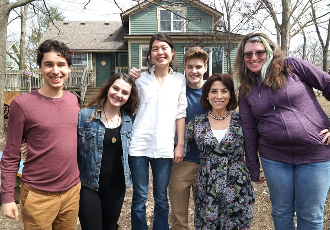 Those hanging out at the Living and Learning Center on March 29 include, from left: Dominic Zarnecki, mentor Silvia Robazzo, Angelica Tao, Gage Farrow, center director Rachelle Vartanian, and Delaney Sheridan. The home on Griswold that houses the center is seen at rear.