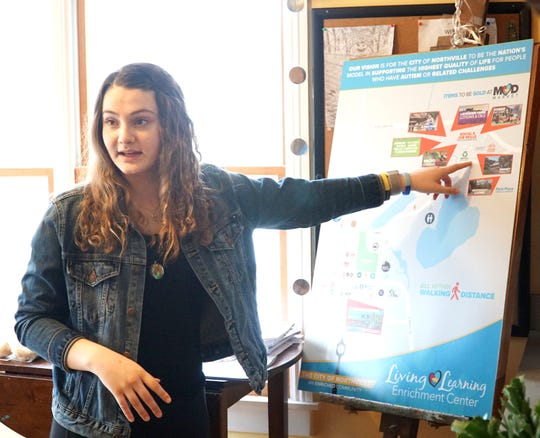 Living and Learning Center mentor Silvia Robazzo points to a map that shows the center's aspirations: to acquire the nearby Massey property and turn it into a potential residential and drop-in center for teens with autism and aspergers.