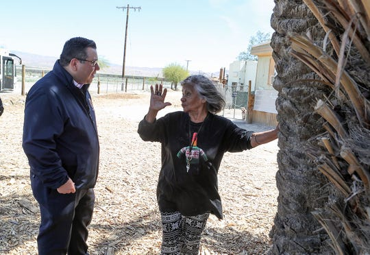 Eduardo Garcia, left, talks with Connie Hernandez who lives in the Desert View Mobile Home Park in Thermal where the water is supplied by a domestic well, March 29, 2019.