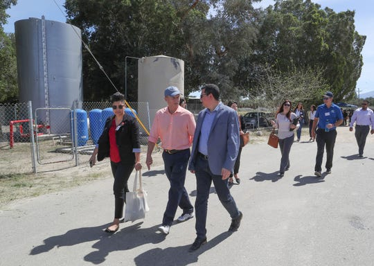 Tom Steyer, center with hat, tours the Desert Rose Mobile Home Park where the residential water is supplied by a domestic well in Thermal, March 29, 2019.