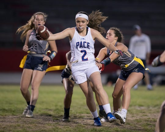 Jaydyn Walters (99) and Sophi Doerr (2) get the flag pull on Makayla Michael (2) as she carries the ball during the Gulf Breeze vs Pace flag football game at Pace High School on Wednesday, March 27, 2019.