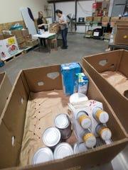 Amanda Thomas, an employee at Feeding the Gulf Coast, works Friday with volunteer Cari Milton on sorting food at the Santa Rosa County area food bank.