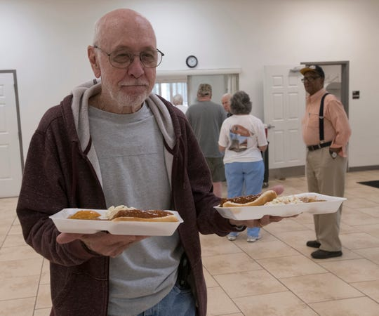 Harvey Kingry picks up lunch provided by the Council on Aging of West Florida for himself and his wife at the Bagdad Community Center on Friday.