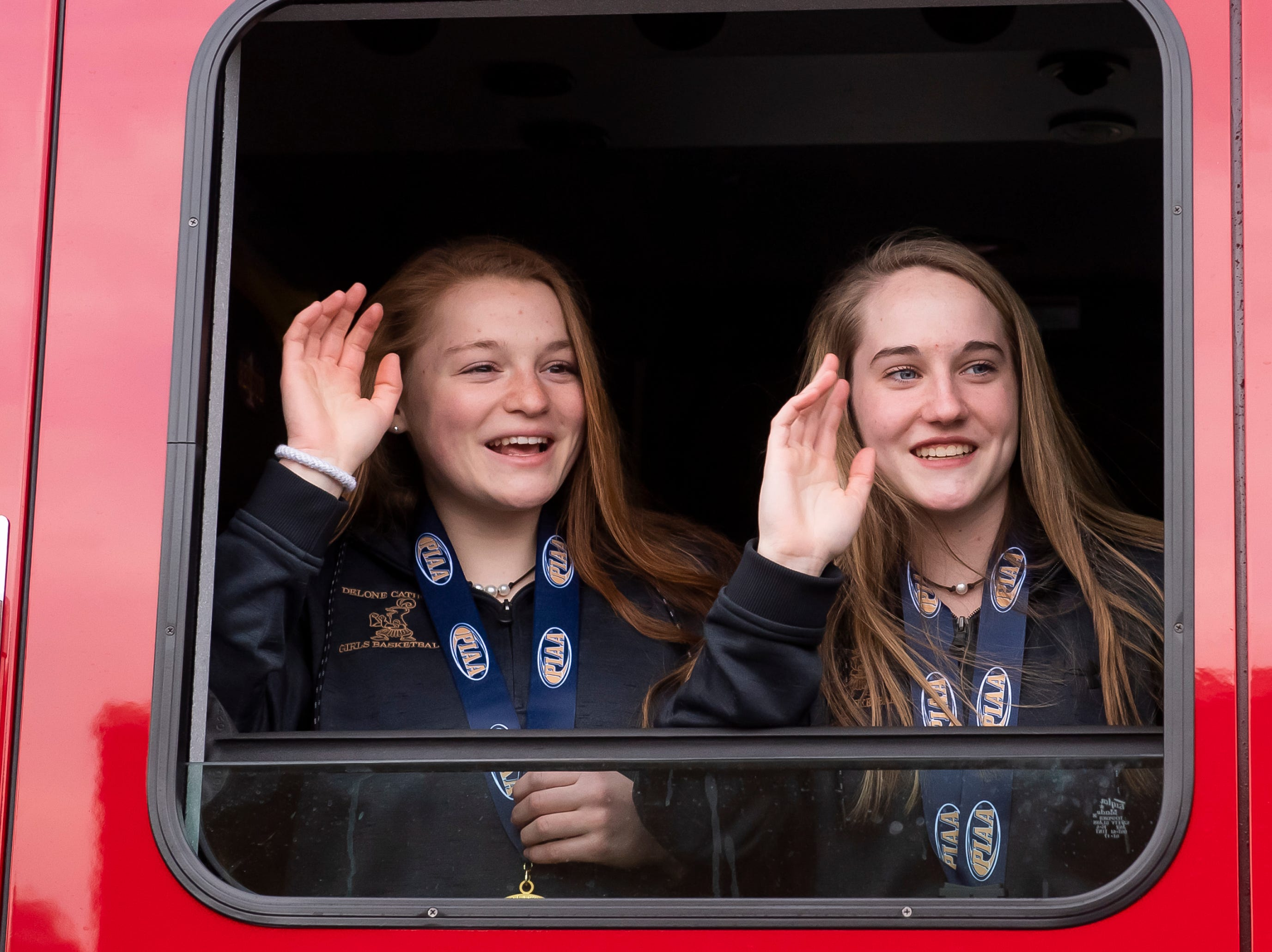Members of the Delone Catholic girls basketball team wave to the crowd from inside a firetruck during a parade celebrating their PIAA championship on Thursday, March 28, 2019.