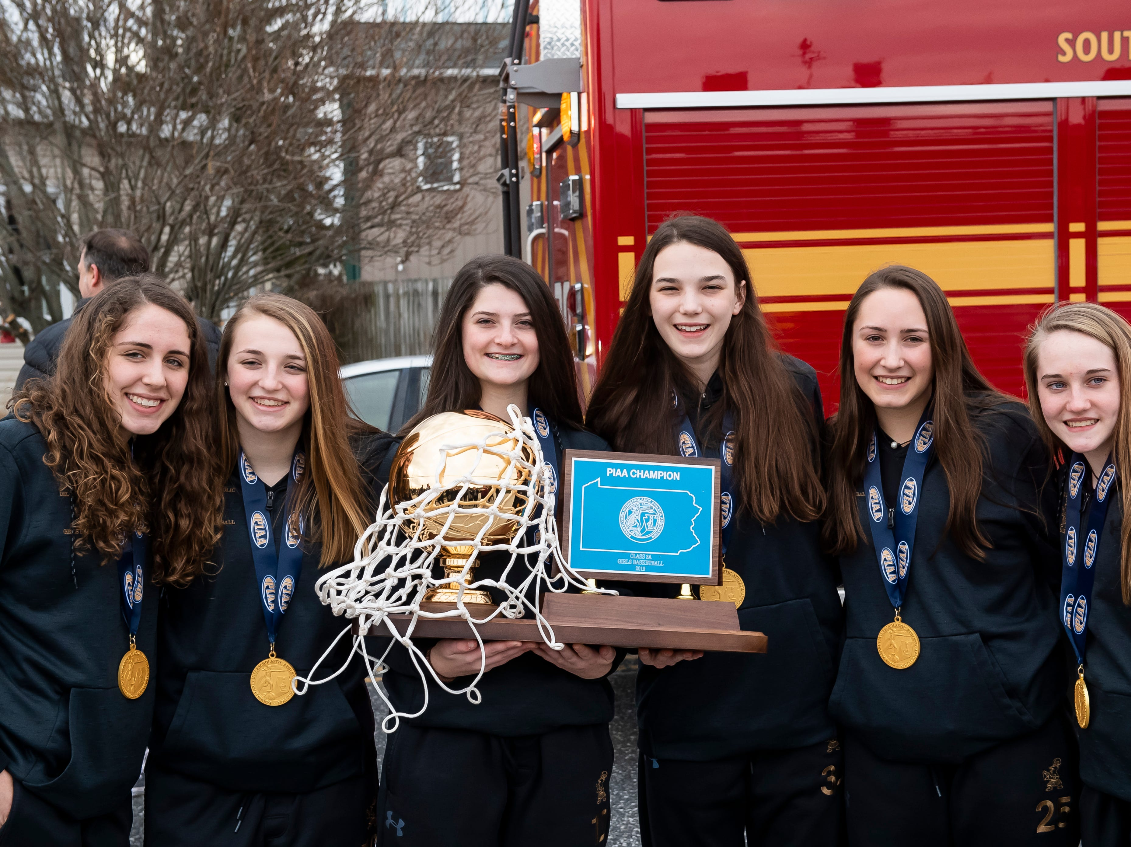 Members of the Delone Catholic girls basketball team pose for photos following a parade in McSherrystown celebrating their PIAA championship on Thursday, March 28, 2019.