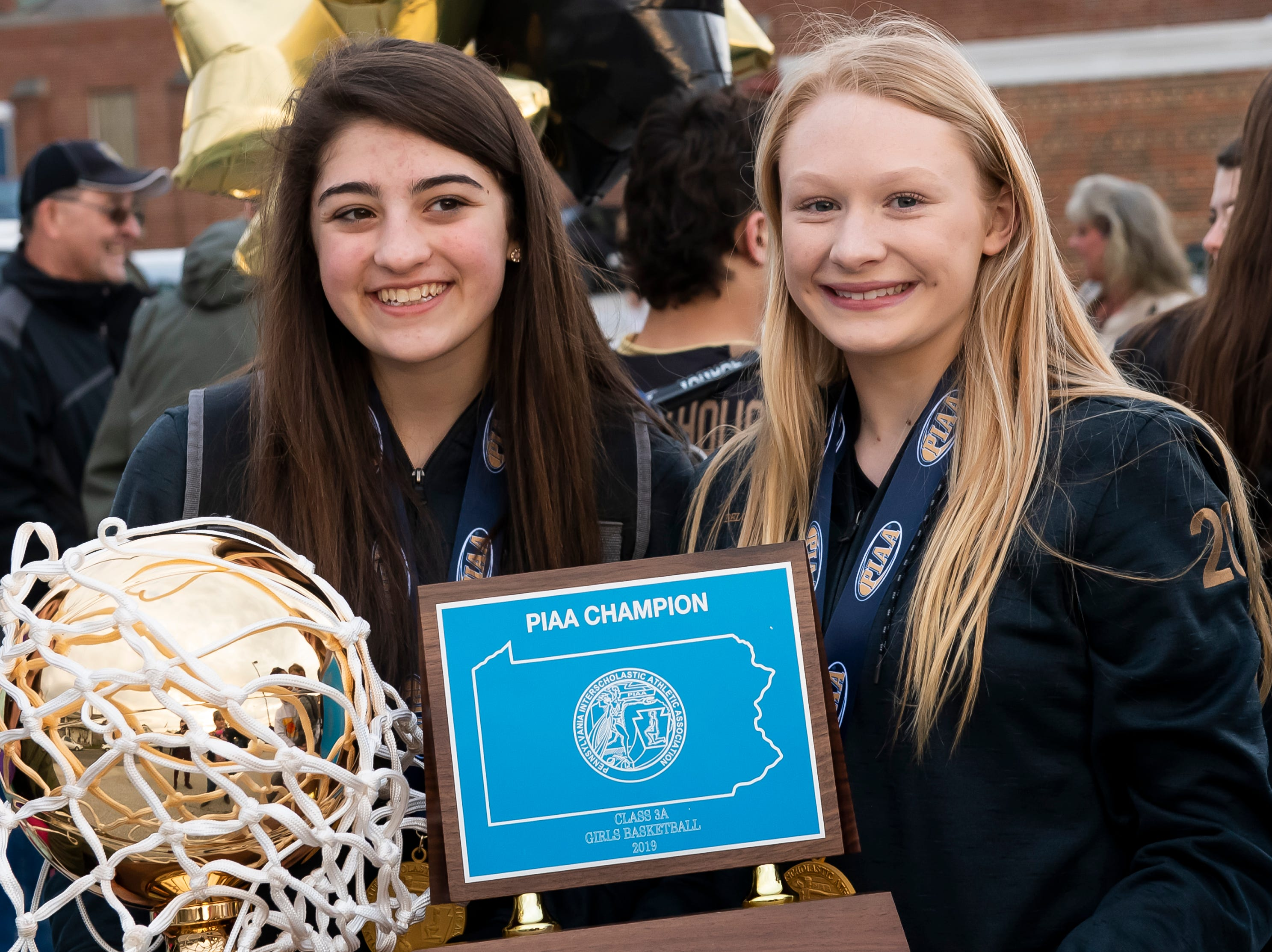 Delone Catholic's Maddie Sieg, left, and Brooke Lawyer pose for photos with the PIAA championship trophy following a parade in McSherrystown on Thursday, March 28, 2019.