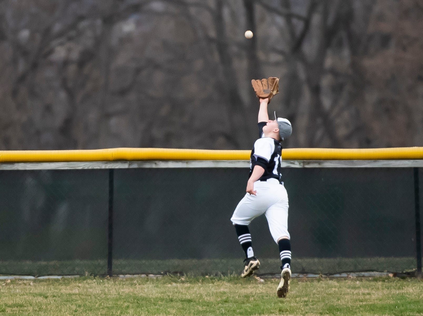 South Western left fielder Ethan Stalnecker comes up just inches short of snagging a deep fly ball during a game against Carlisle in Hanover on Friday, March 29, 2019. The Mustangs won 11-9.