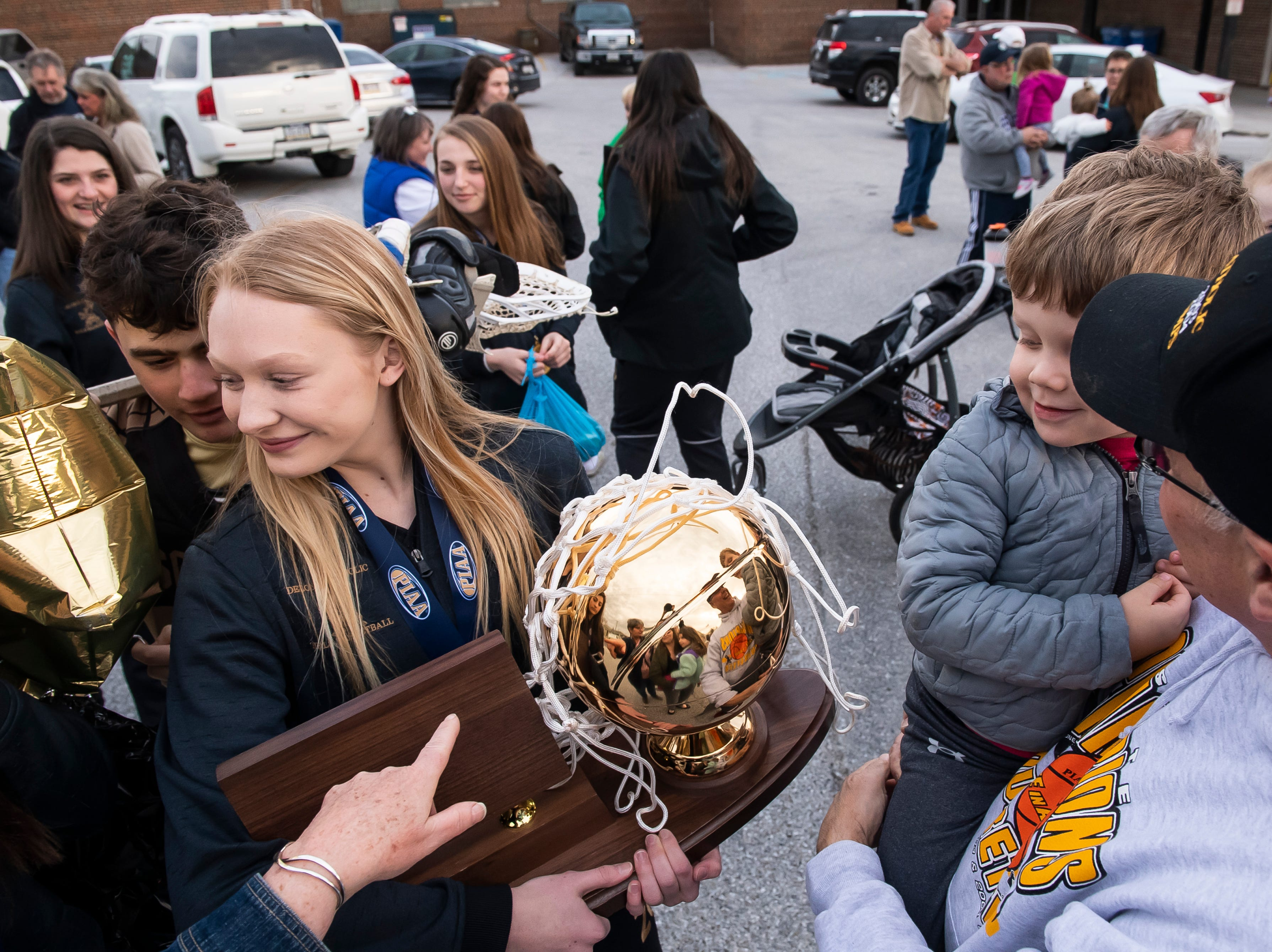 Harrison Bonds, 3, looks at the PIAA championship trophy with some suspicion as his grandfather, Dave Zinn, holds him in his arms following a parade in McSherrystown celebrating the Squirettes' state championship on Thursday, March 28, 2019. Zinn's daughter, Jana Bonds, was a member of the Squirettes' 2003 and 2004 PIAA championship teams.