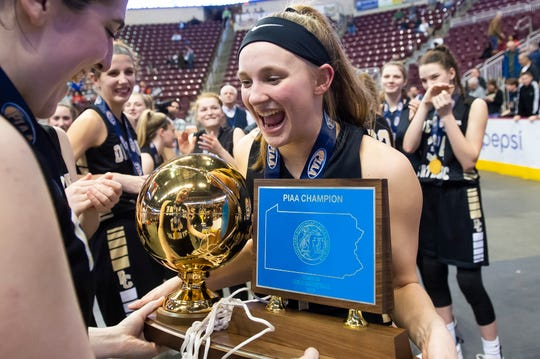 Delone Catholic's Riley Vingsen, right, hold the PIAA trophy after the Squirettes won the PIAA 3A championship game at the Giant Center in Hershey on Thursday, March 21, 2019. The Squirettes defeated Dunmore 49-43.