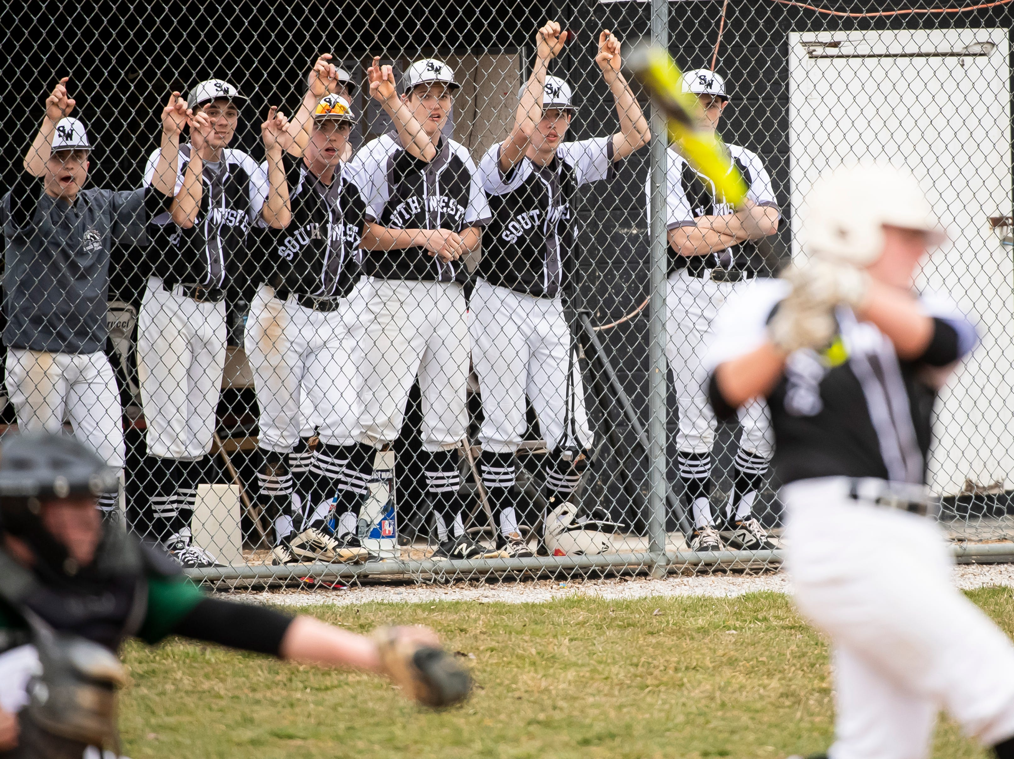 The South Western dugout watches as Ethan Stalnecker takes a swing during a game against Carlisle in Hanover on Friday, March 29, 2019. The Mustangs won 11-9.