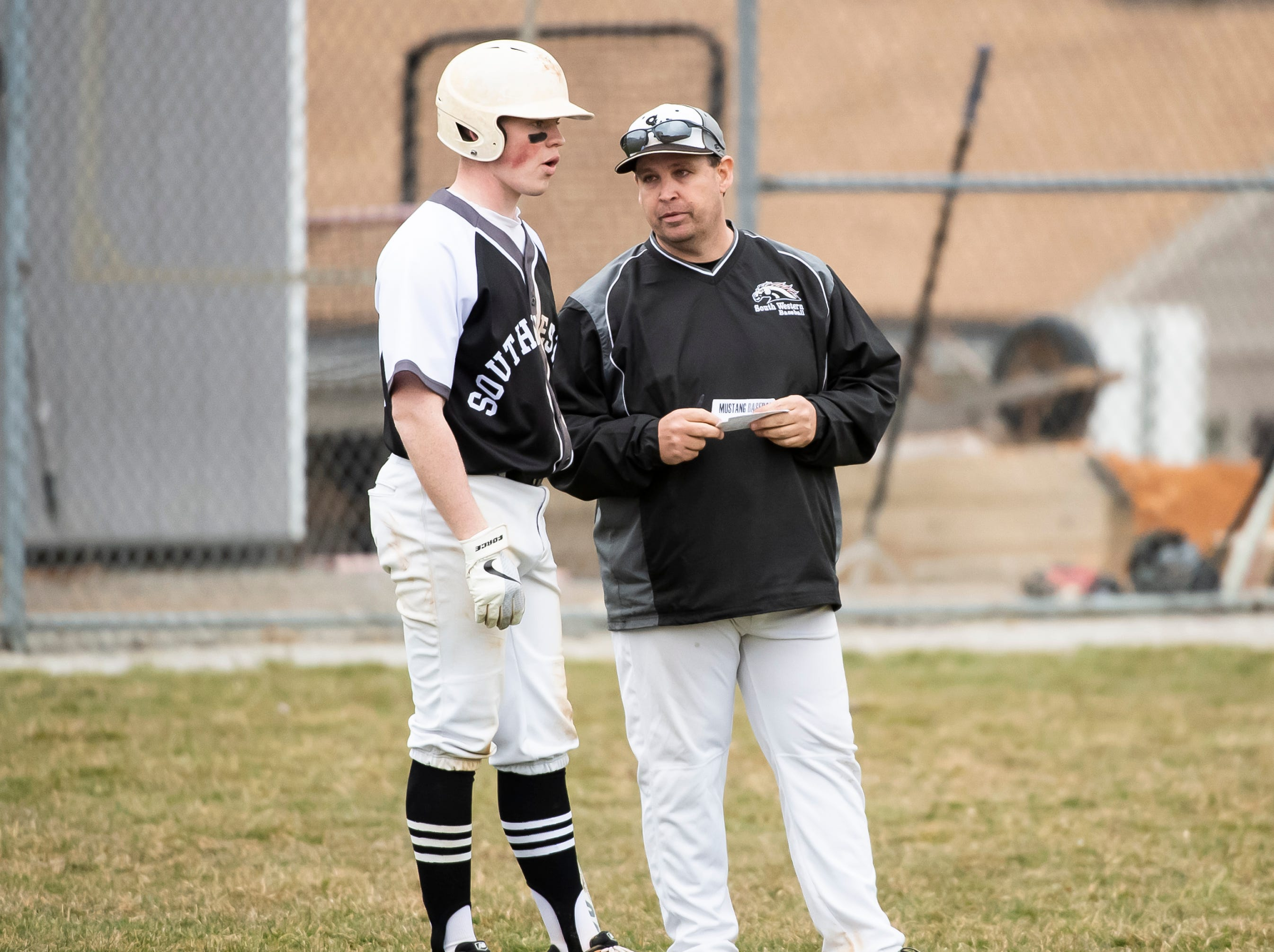 South Western's Josh Tippin speaks with head coach Mike Resetar during a pause in play against Carlisle in Hanover on Friday, March 29, 2019. The Mustangs won 11-9.