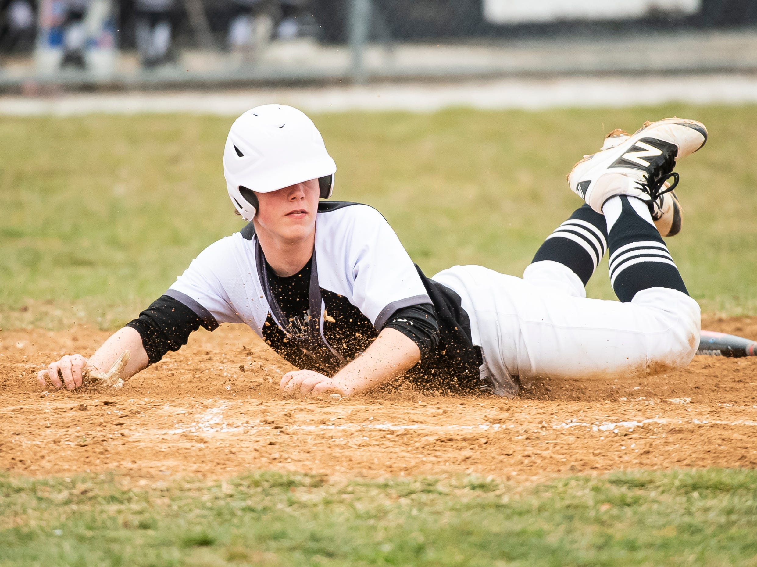 South Western's Ty Cromer dives across home plate to score a run during a game against Carlisle in Hanover on Friday, March 29, 2019. The Mustangs won 11-9.