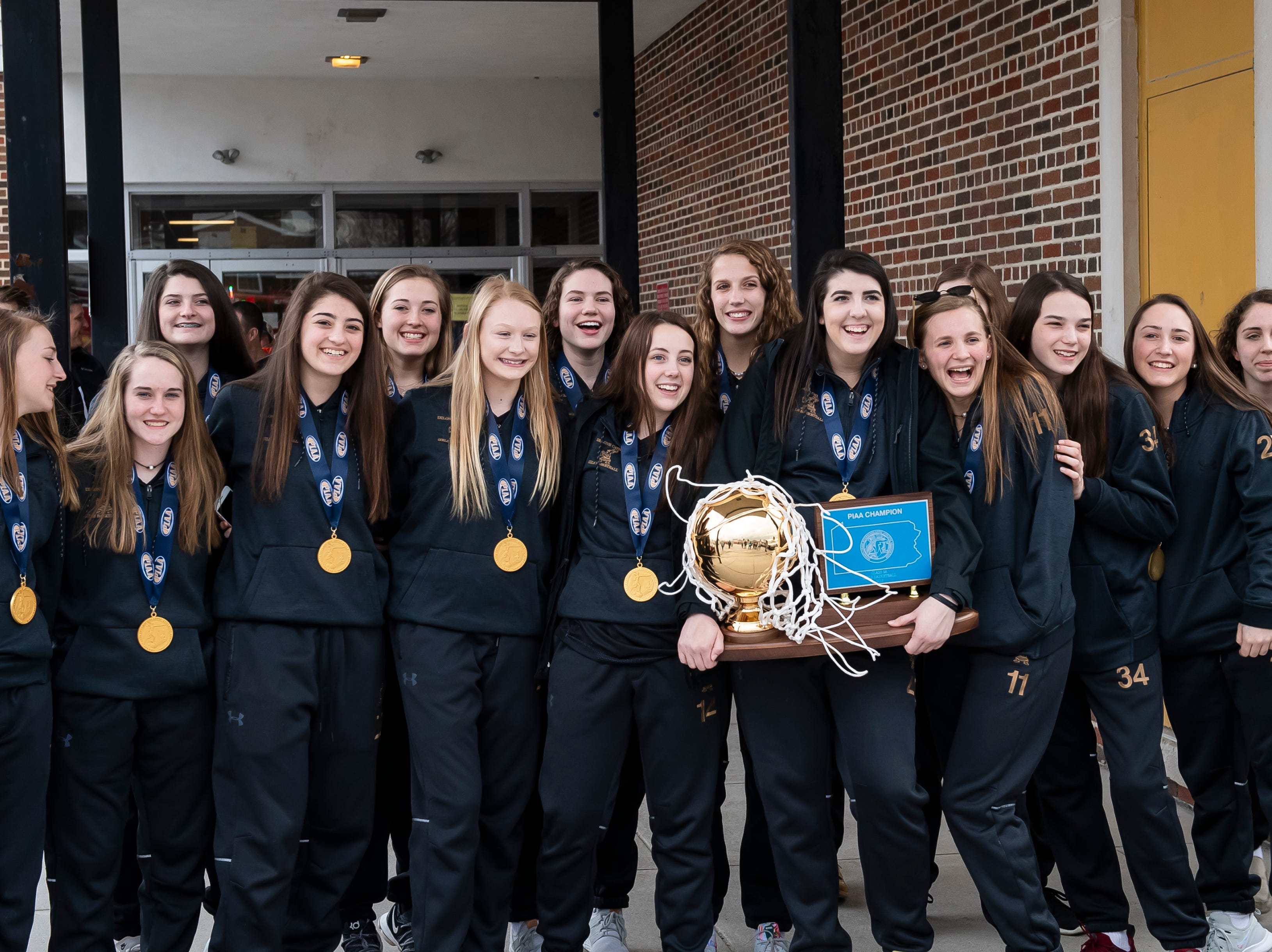 Members of the Delone Catholic 2018-2019 girls basketball team pose for photos before the start of a parade in McSherrystown celebrating their PIAA championship on Thursday, March 28, 2019.