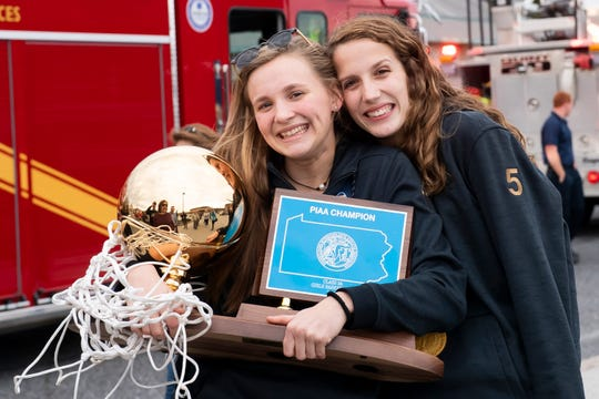 Delone Catholic's Riley Vingsen, left, and Maggie Wells pose for a photo together following a parade in McSherrystown celebrating the Squirettes' PIAA championship on Thursday, March 28, 2019.