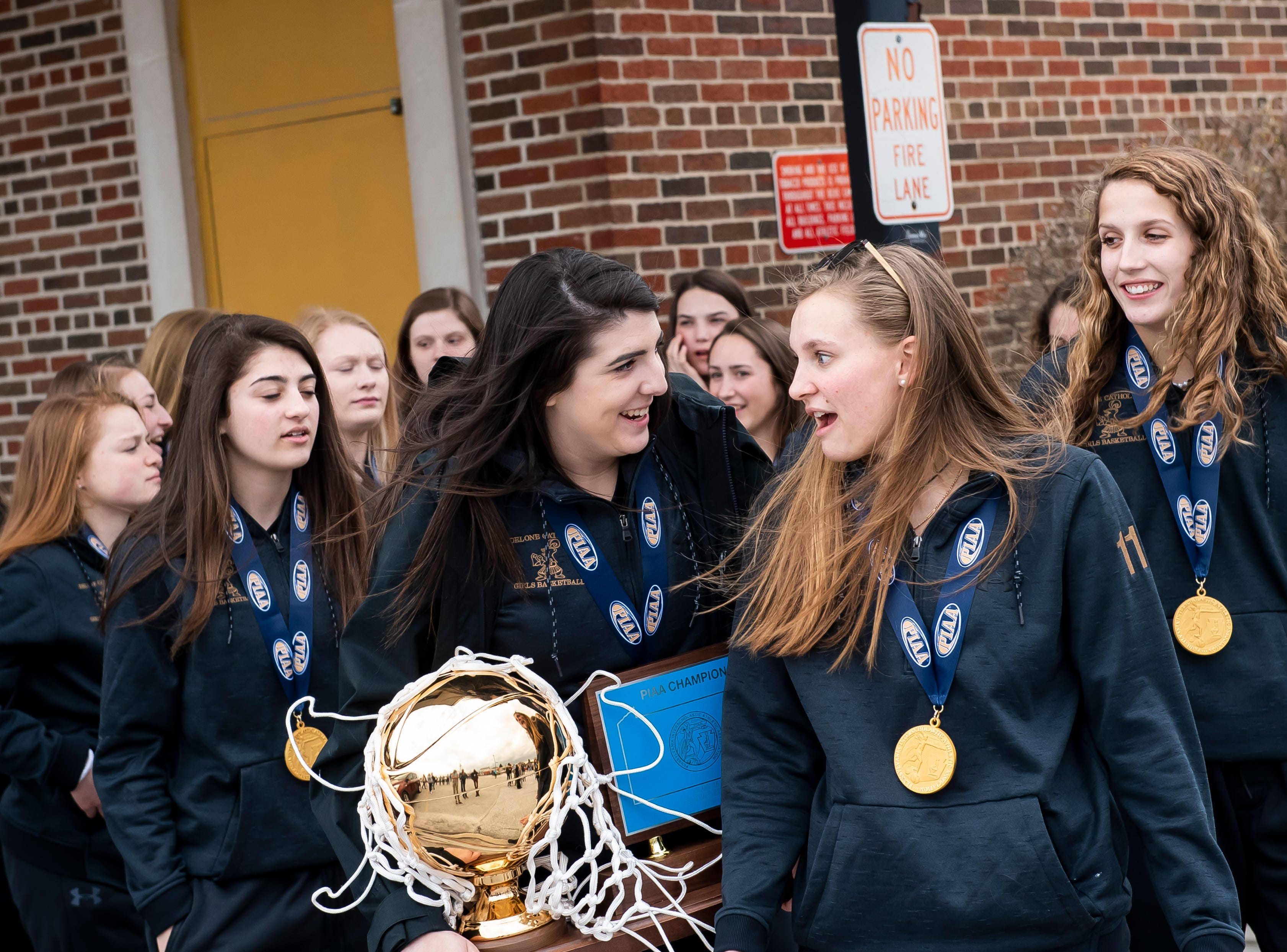Delone Catholic's Bradi Zumbrum and Riley Vingsen lead the Squirettes before the start of a parade in McSherrystown celebrating their PIAA championship on Thursday, March 28, 2019.