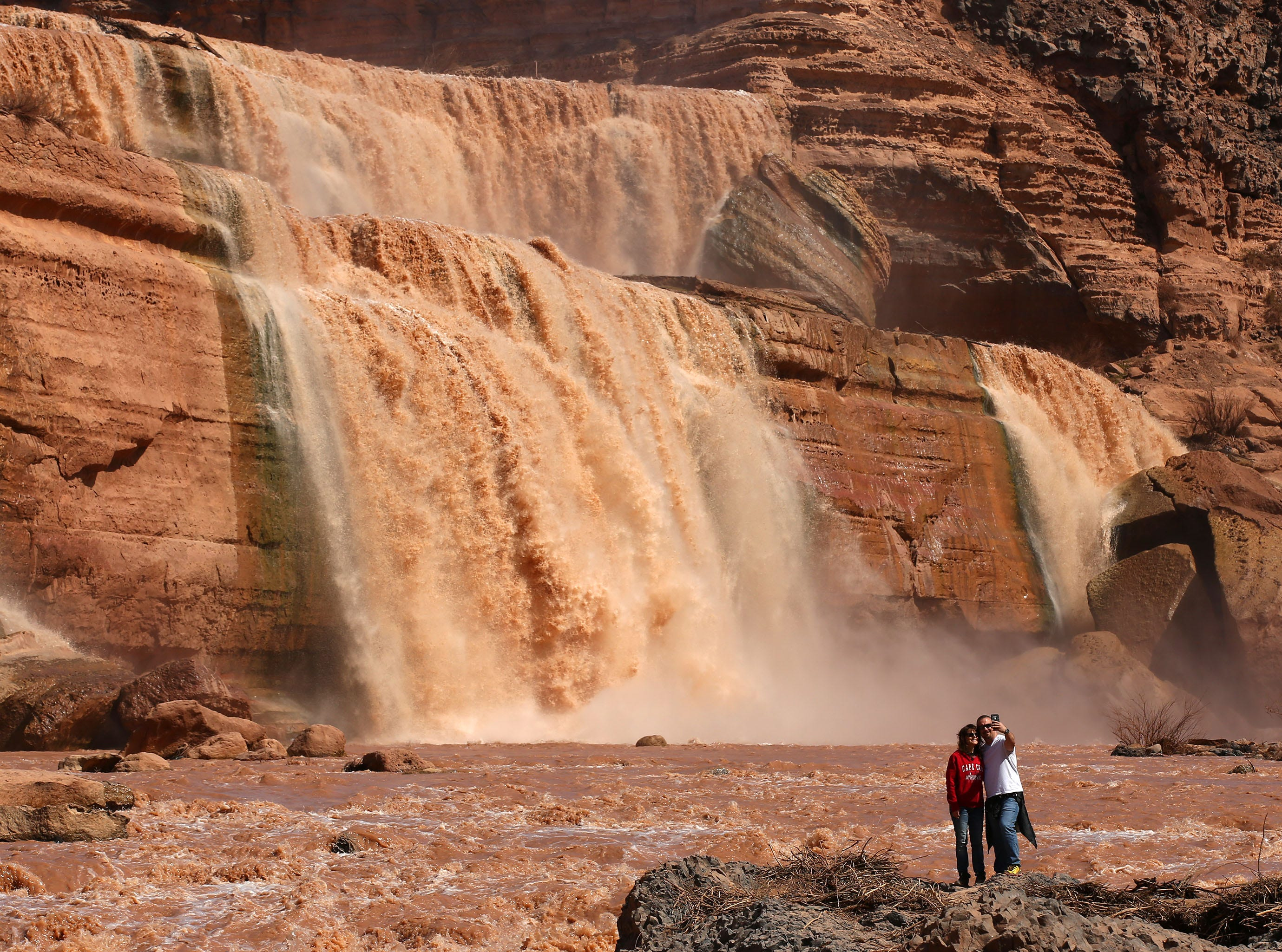 Tourists take a selfie at Grand Falls in the Painted Desert on the Navajo Nation on March 28, 2019, near Leupp, Arizona. Melted snow and rain travels down the Little Colorado River to the 185-foot fall a.k.a. Chocolate Falls. Grand Falls is 18 feet taller than Niagara Falls.