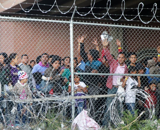 Central American migrants wait for food in El Paso, Texas on March 27, 2019, in a pen erected by U.S. Customs and Border Protection to process a surge of migrant families and unaccompanied minors.