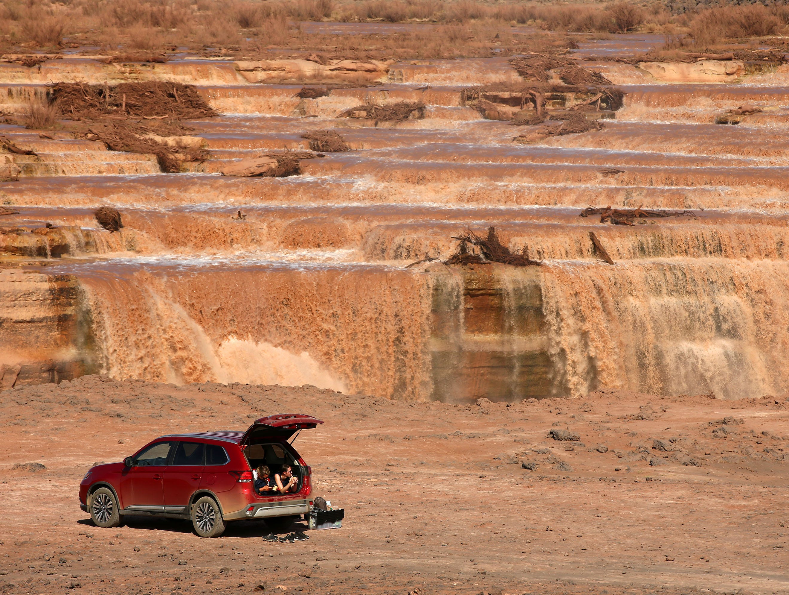 A tourist from Switzerland takes a midday break in a car at Grand Falls in the Painted Desert on the Navajo Nation on March 28, 2019, near Leupp, Arizona. Melted snow and rain travels down the Little Colorado River to the 185-foot fall a.k.a. Chocolate Falls. Grand Falls is 18 feet taller than Niagara Falls.