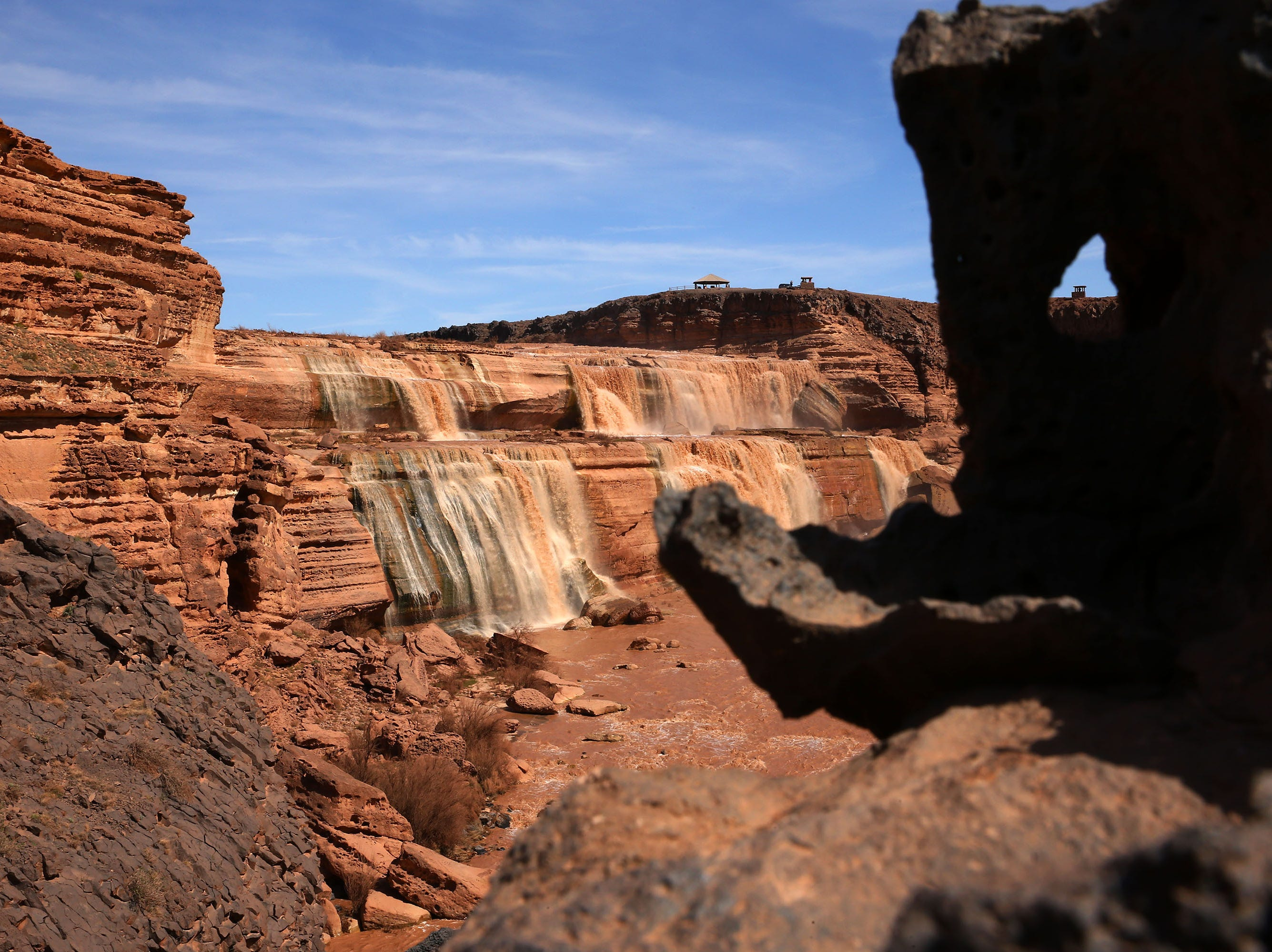 Volcanic rock formation above Grand Falls in the Painted Desert on the Navajo Nation on March 28, 2019, near Leupp, Arizona. Melted snow and rain travels down the Little Colorado River to the 185-foot fall a.k.a. Chocolate Falls. Grand Falls is 18 feet taller than Niagara Falls.