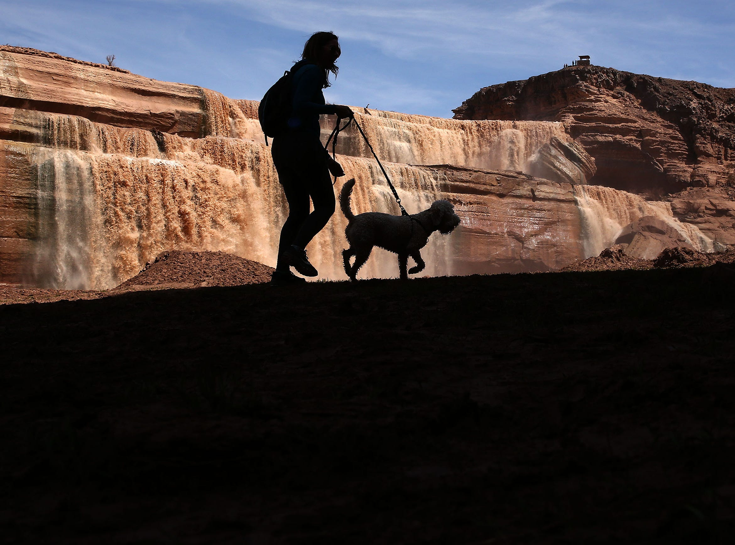 Sunny St. John walks Indiana at Grand Falls in the Painted Desert on the Navajo Nation on March 28, 2019, near Leupp. Melted snow and rain travels down the Little Colorado River to the 185-foot fall a.k.a. Chocolate Falls. Grand Falls is 18 feet taller than Niagara Falls.