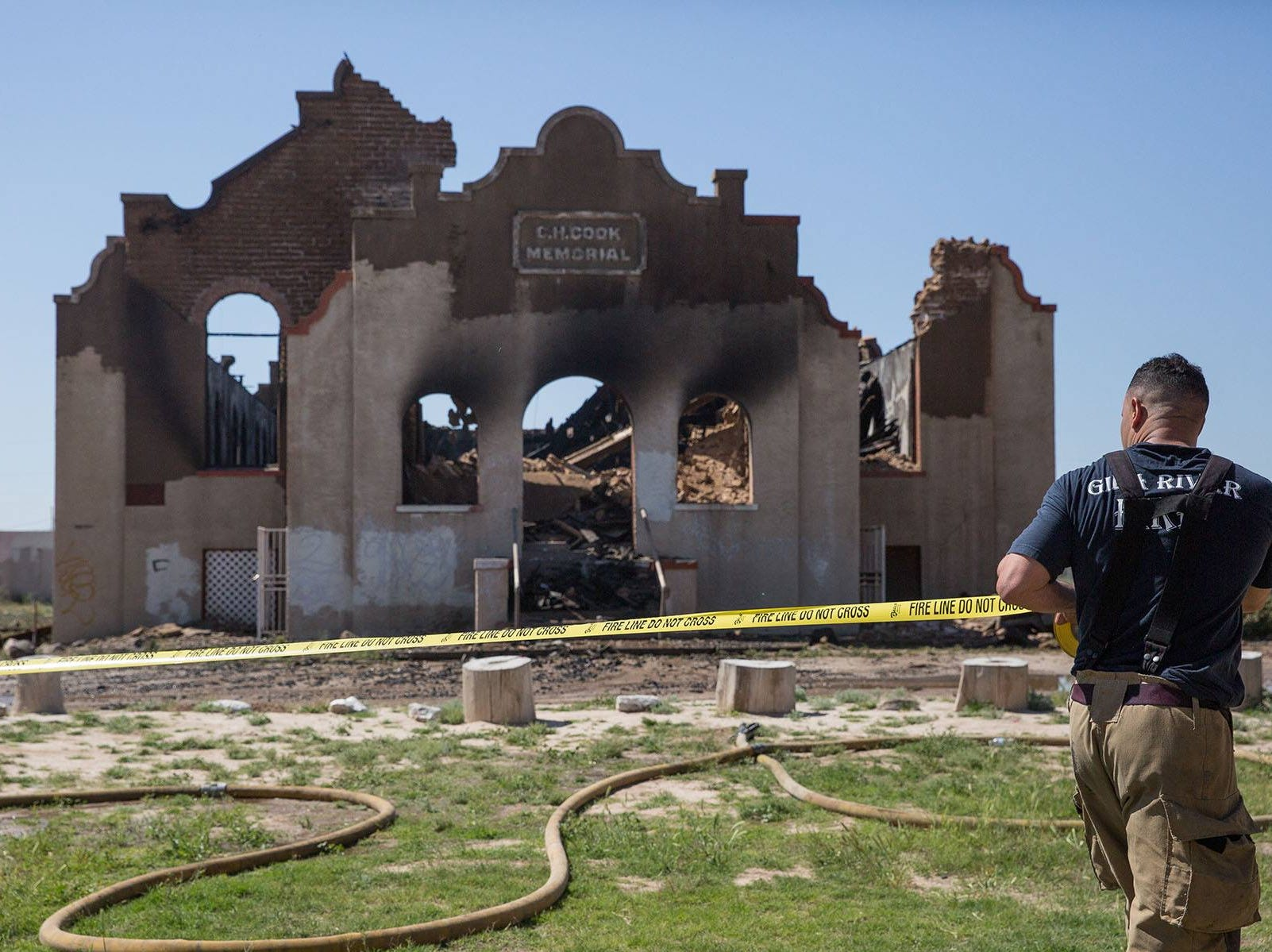 A Gila River fire fighter brings police tape across the front yard of the church after the fire was extinguished.