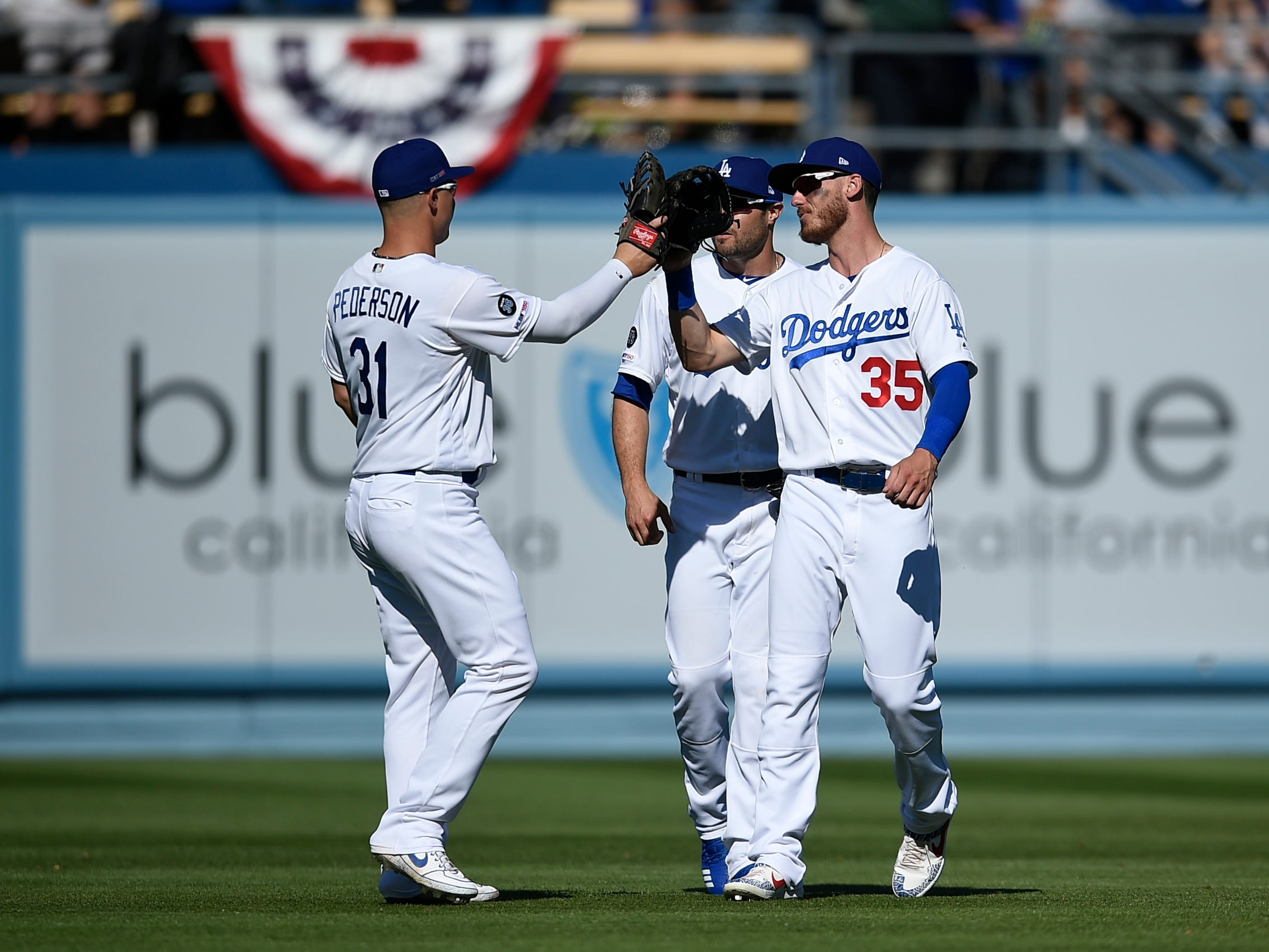 Mar 28, 2019; Los Angeles, CA, USA; Los Angeles Dodgers right fielder Cody Bellinger (35) celebrates with left fielder Joc Pederson (31) after the game as center fielder A.J. Pollock (11) looks on against the Arizona Diamondbacks at Dodger Stadium.
