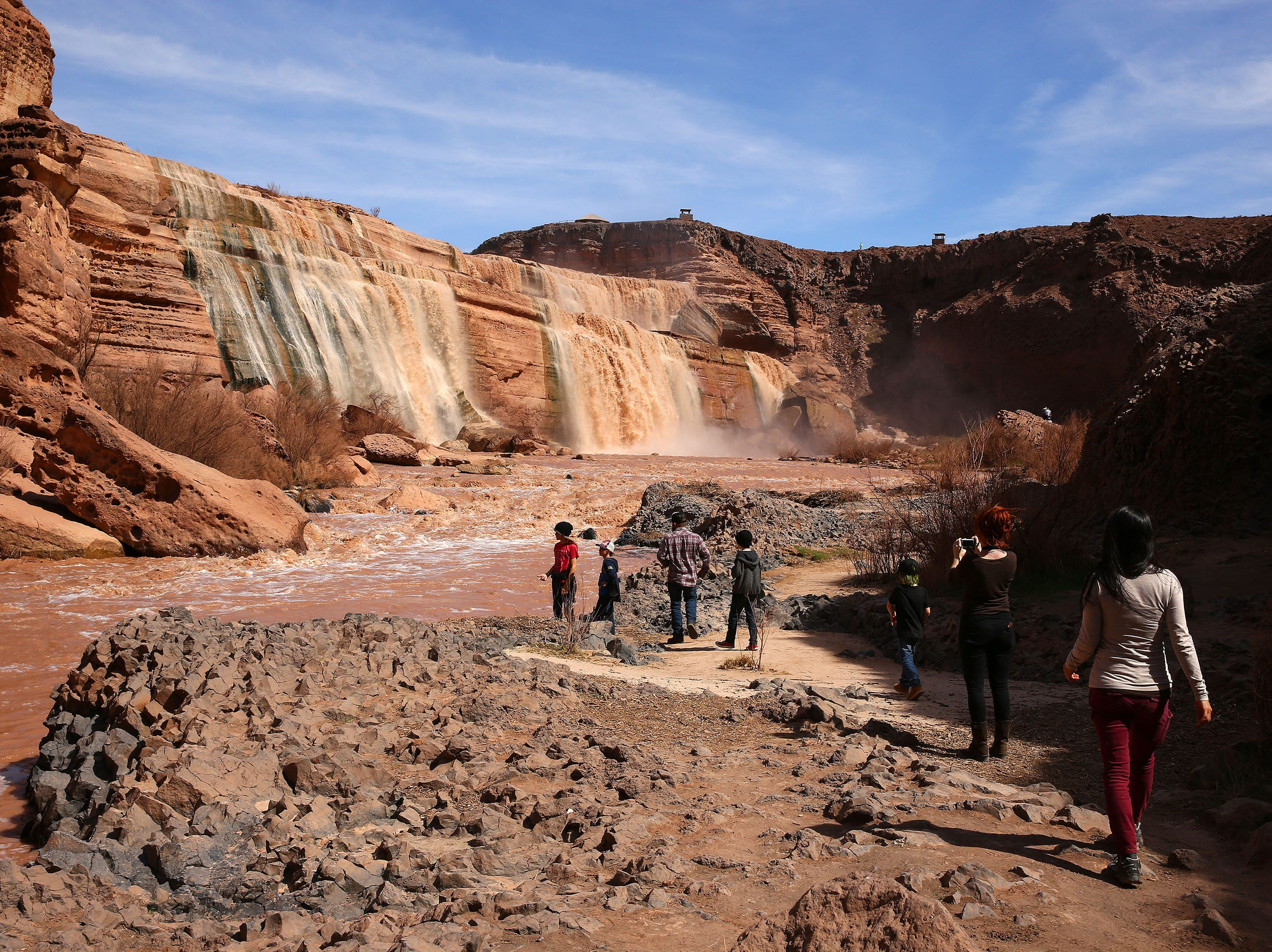Tourists hike into the canyon for a waterside view of Grand Falls in the Painted Desert on the Navajo Nation on March 28, 2019, near Leupp, Arizona. Melted snow and rain travels down the Little Colorado River to the 185-foot fall a.k.a. Chocolate Falls. Grand Falls is 18 feet taller than Niagara Falls.
