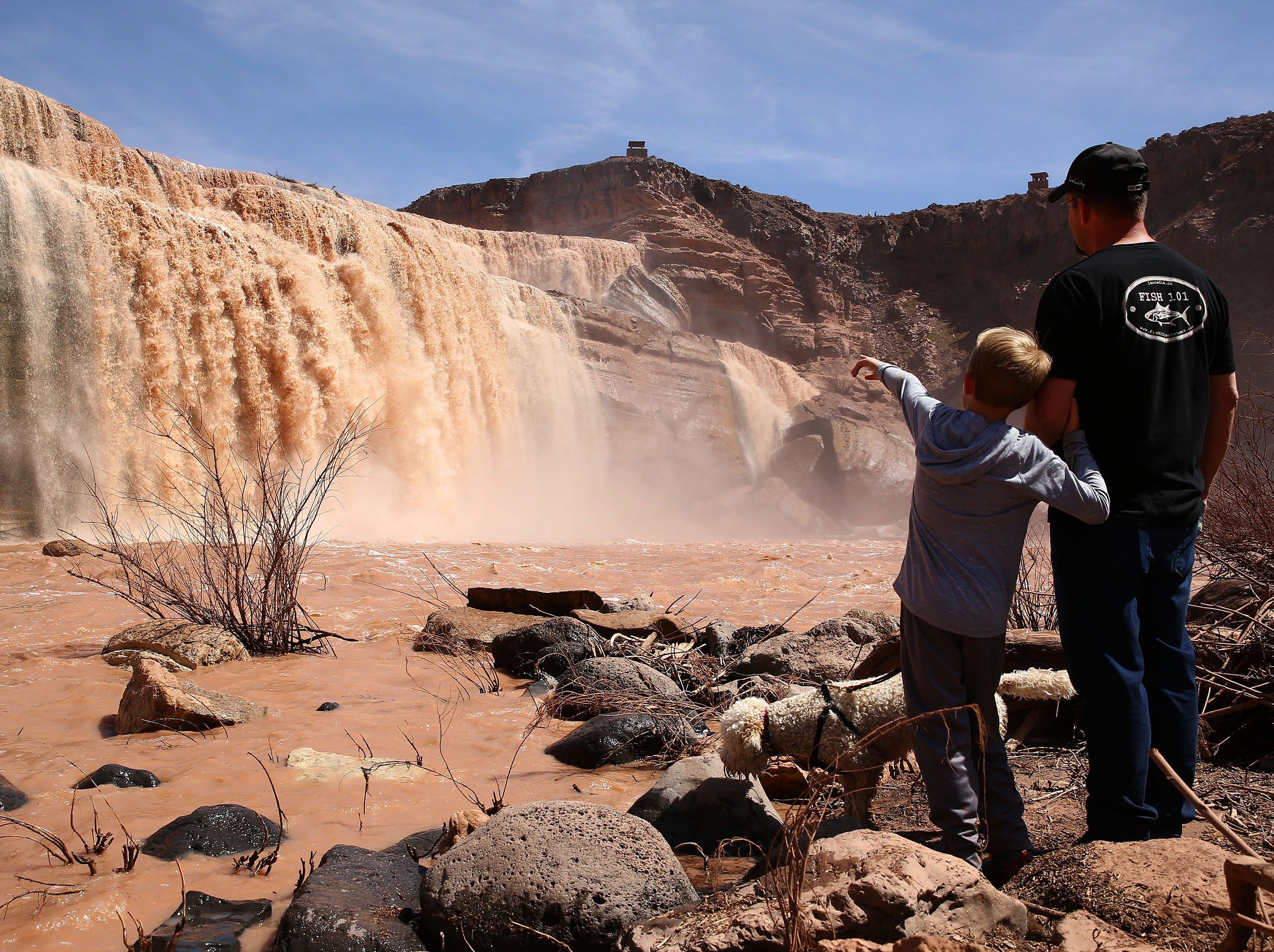 Andy St. John and his son Luke enjoy the view of Grand Falls in the Painted Desert on the Navajo Nation on March 28, 2019, near Leupp, Arizona. Melted snow and rain travels down the Little Colorado River to the 185-foot fall a.k.a. Chocolate Falls. Grand Falls is 18 feet taller than Niagara Falls.