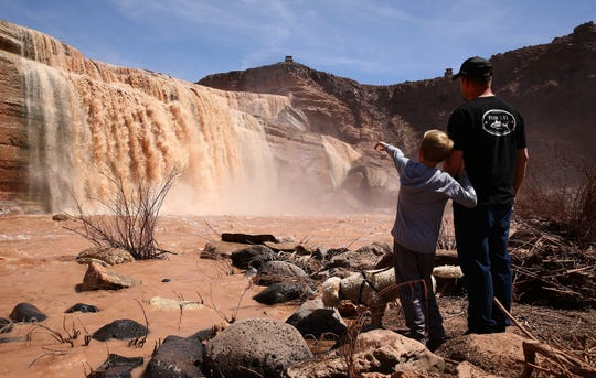 Andy St. John and his son Luke enjoy the view of Grand Falls in the Painted Desert on the Navajo Nation on Mar. 28, 2019 near Leupp, Ariz.