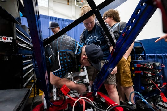 Richmond Blue Devils sophomore Melissa Rochon, right, watches coach Brandon Potts make several last-minute adjustments to their robot before the FIRST Robotics district event Friday, March 29, 2019 at Marysville High School.