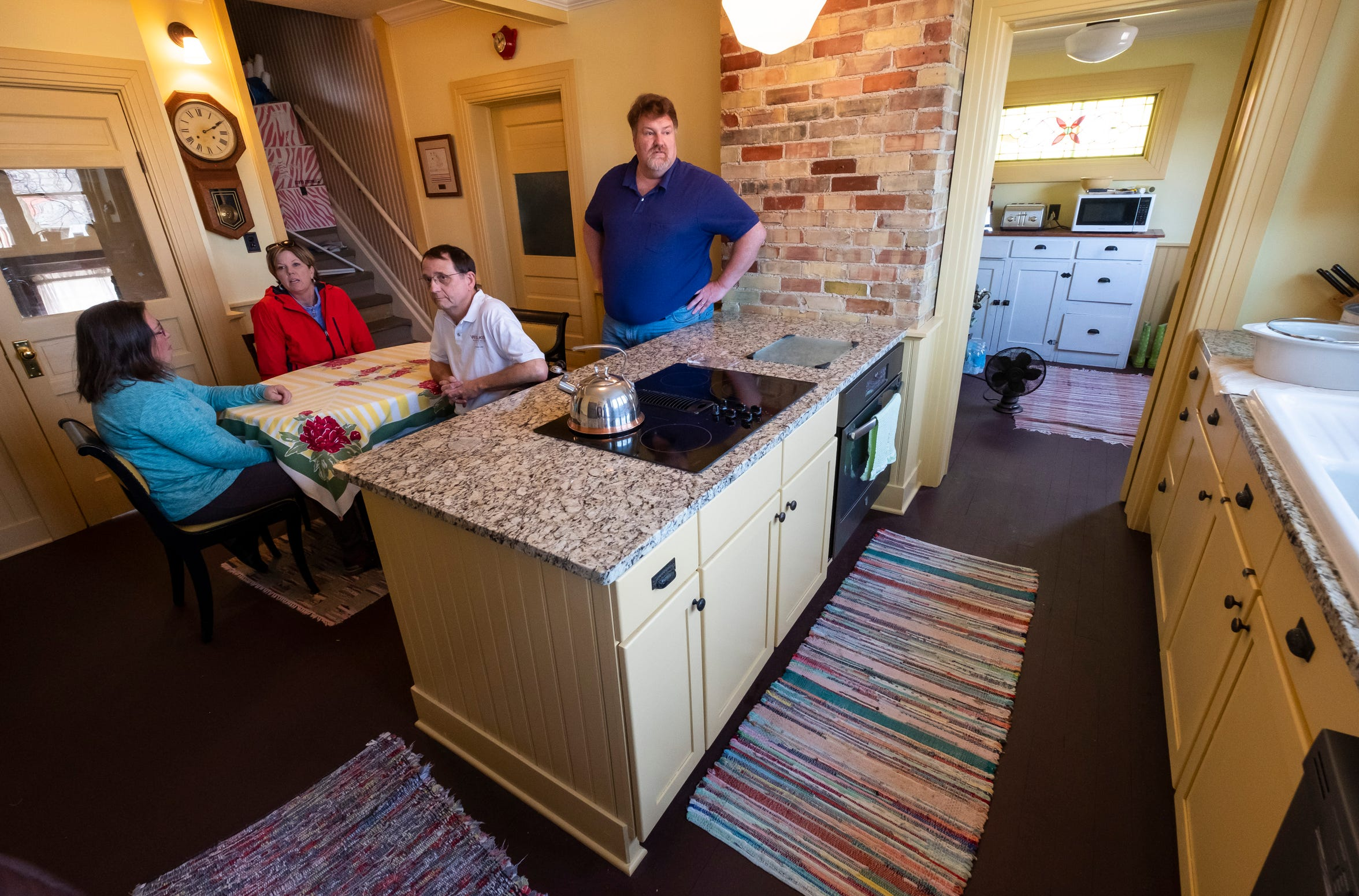 Olde Town residents Kevin and Bamy Banker, left and second to right, Cheri Smith, second to left, and Chris Troy discuss efforts to revitalize the neighborhood Friday, March 29, 2019 in the remodelled kitchen of Chris Troy's home. Olde Town residents feared the Center's original Central Business District rezoning request would've put a damper on the neighborhood's revitalization, but the request was withdrawn Wednesday.