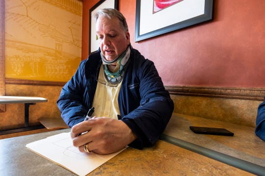 Pat Coughlin, who owns one of the buildings that makes up Riverview Plaza in St. Clair, draws a diagram showing some of the changes that will be made to the plaza's parking lot this summer. A gated system will be installed that allows people who want to use the lot and shop at the plaza to park for free, but will charge people who do not shop at the plaza.