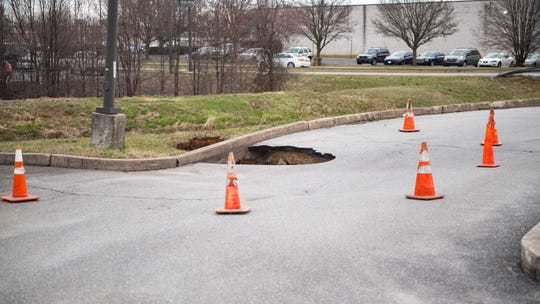 The sinkhole extends from the parking lot and continues under the curb to the ground on the other side, March 28, 2019.