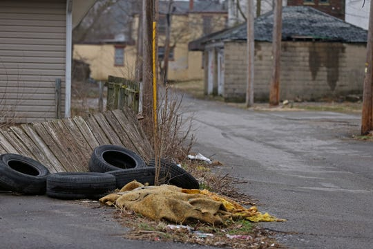 Tires and other trash sit in an alley between North 12th and 13th streets in Richmond.