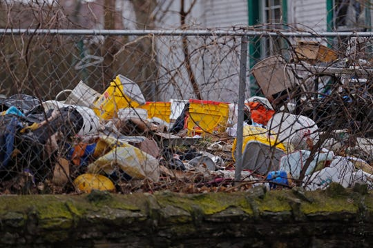 Trash litters a yard in the 1300 block of North C Street in Richmond.