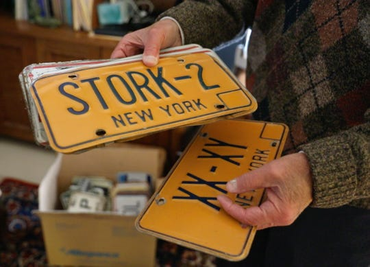 Victor Poleshuck sorts through some of the custom license plates he has had on his cars for over thirty years, at his Pittsford home Thursday, March 28, 2019.