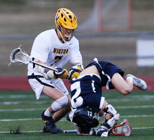 Victor (7) makes this big hit on Pittsford (2) Harrison Cross who kept possession of the ball in lacrosse action Thursday night.