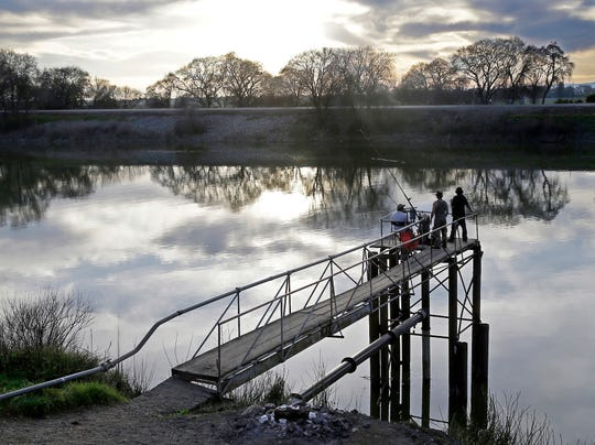 In this Feb. 23, 2016, file photo, fishermen try their luck along the Sacramento River in the San Joaquin-Sacramento River Delta, near Courtland, Calif. The federal government has sued California over water policies it says violate state environmental protections. The lawsuit filed Thursday, March 28, 2019, in federal court in Sacramento challenges a plan that went into effect in December to increase water flows in the San Joaquin River.