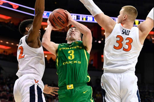Mar 28, 2019; Louisville, KY, United States; Oregon Ducks guard Payton Pritchard (3) goes to the basket as Virginia Cavaliers center Jack Salt (33) and guard De'Andre Hunter (12) during the second half in the semifinals of the south regional of the 2019 NCAA Tournament at KFC Yum Center. Mandatory Credit: Jamie Rhodes-USA TODAY Sports