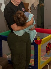 After setting up a playpen, an agent with the U.S. Border Patrol at the Texas Uvalde station holds an 18-month-old whose undocumented mother was taken to the  hospital. Agents cared for the child for two days. Image released: March 29, 2019