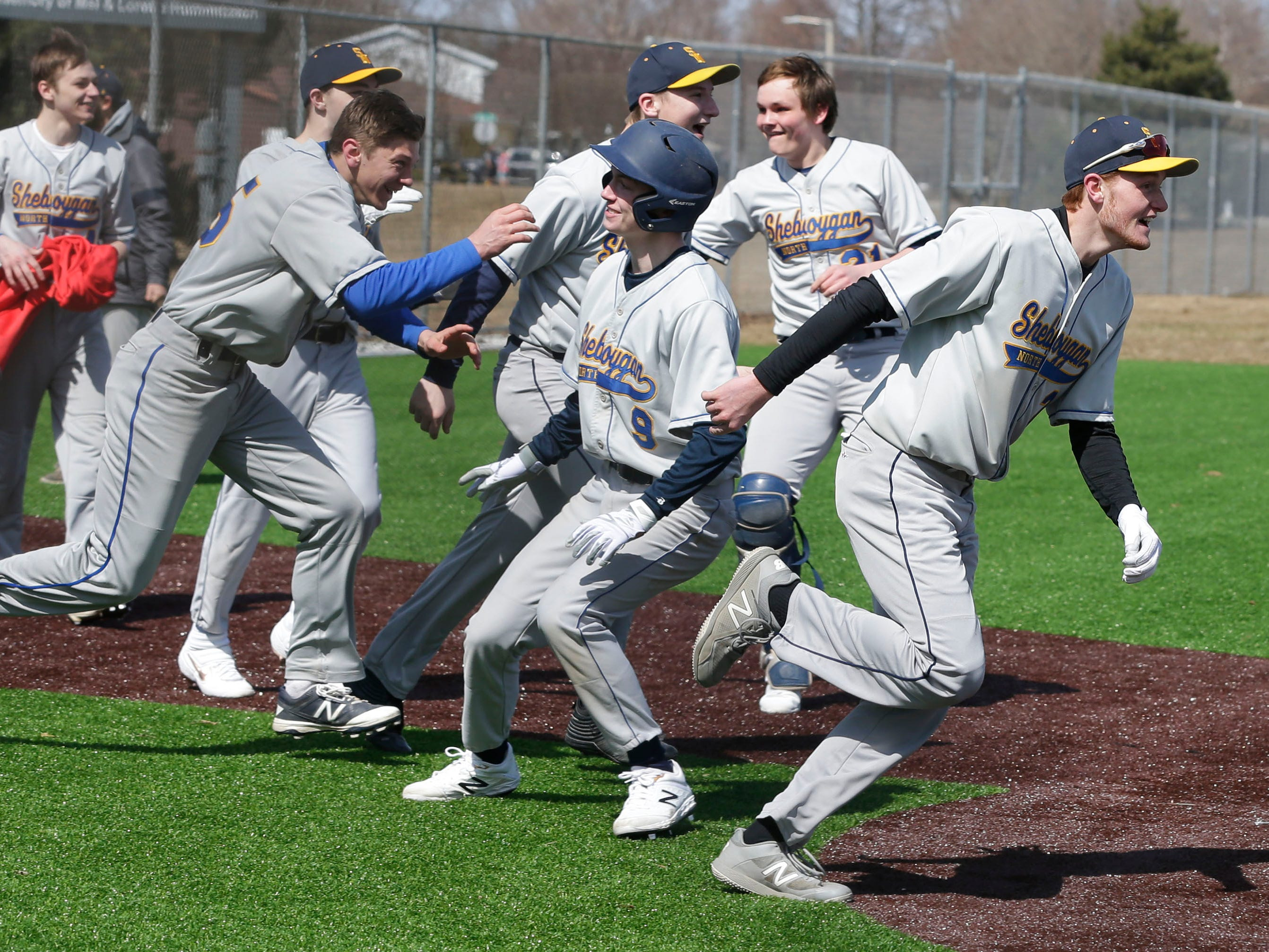 Sheboygan North's baseball team rushes the field following their 7-inning 9-8 win over Appleton North, Friday, March 29, 2019, at the Field of Dreams complex in Sheboygan, Wis.