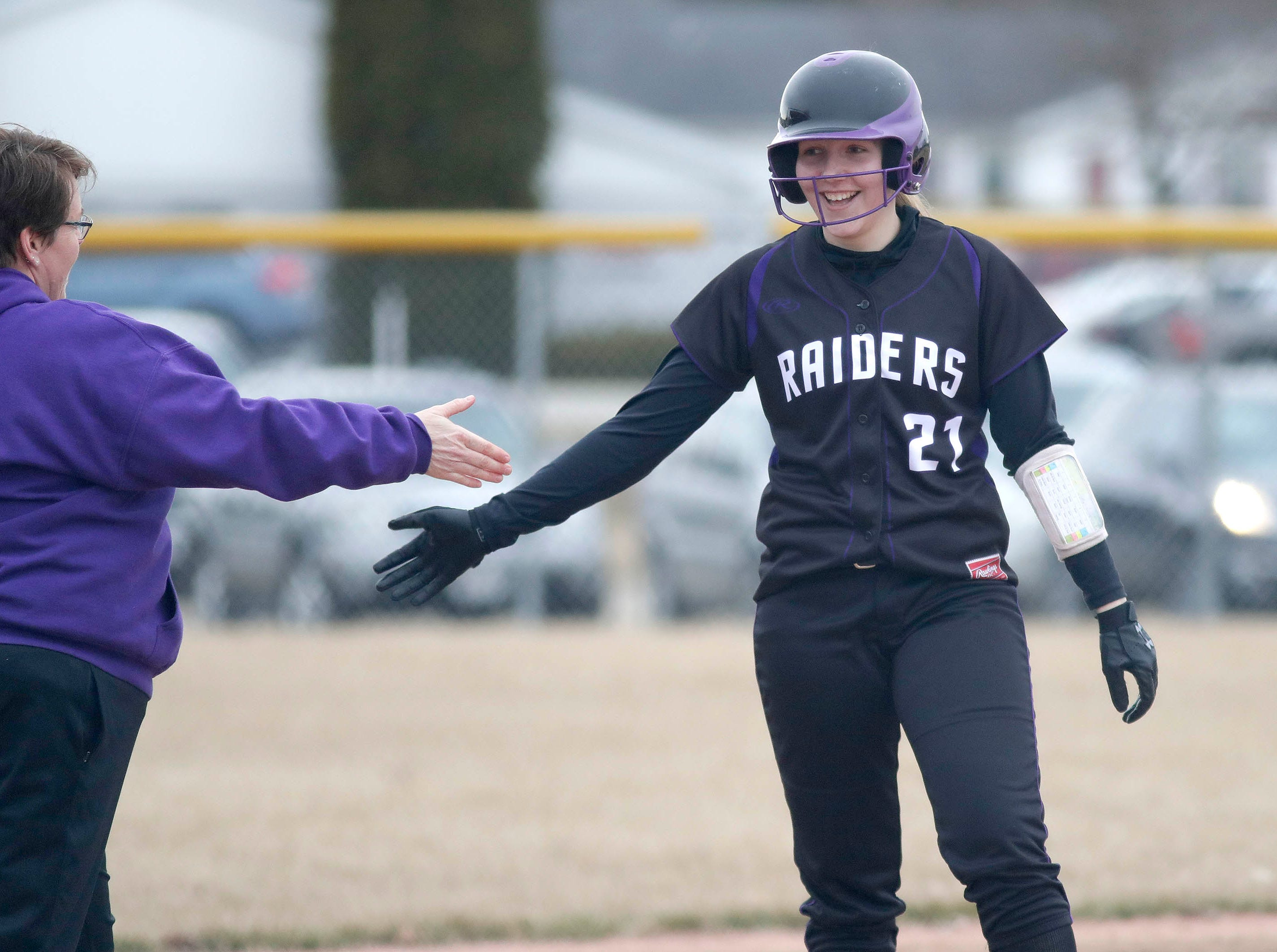Kiel's Andrea Meyer (21) smiles as she made it to third base against Winnebago Lutheran, Thursday, March 28, 2019, in Fond du Lac, Wis.