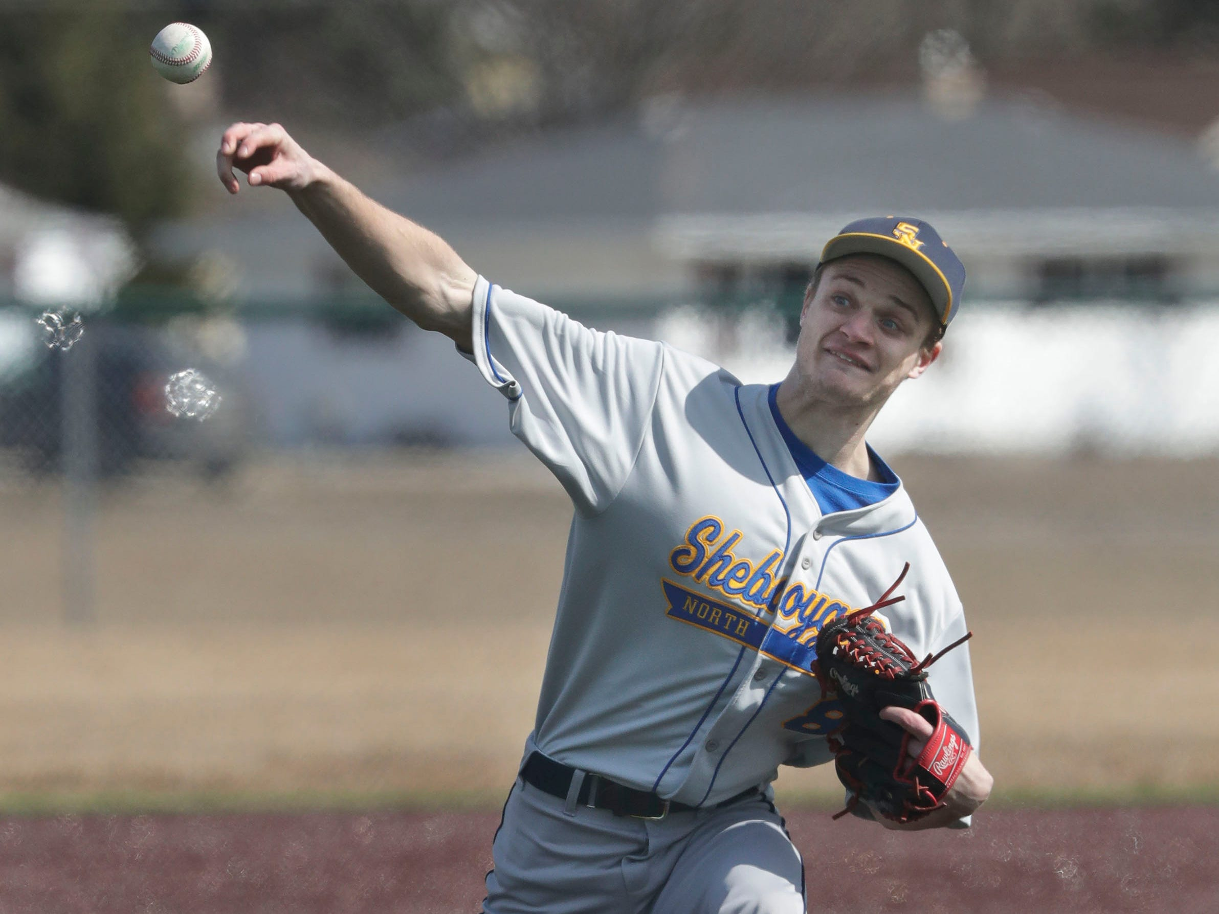 Ethan Scherg (8) winds out a pitch to Appleton North, Friday, March 29, 2019, at the Field of Dreams complex in Sheboygan, Wis.