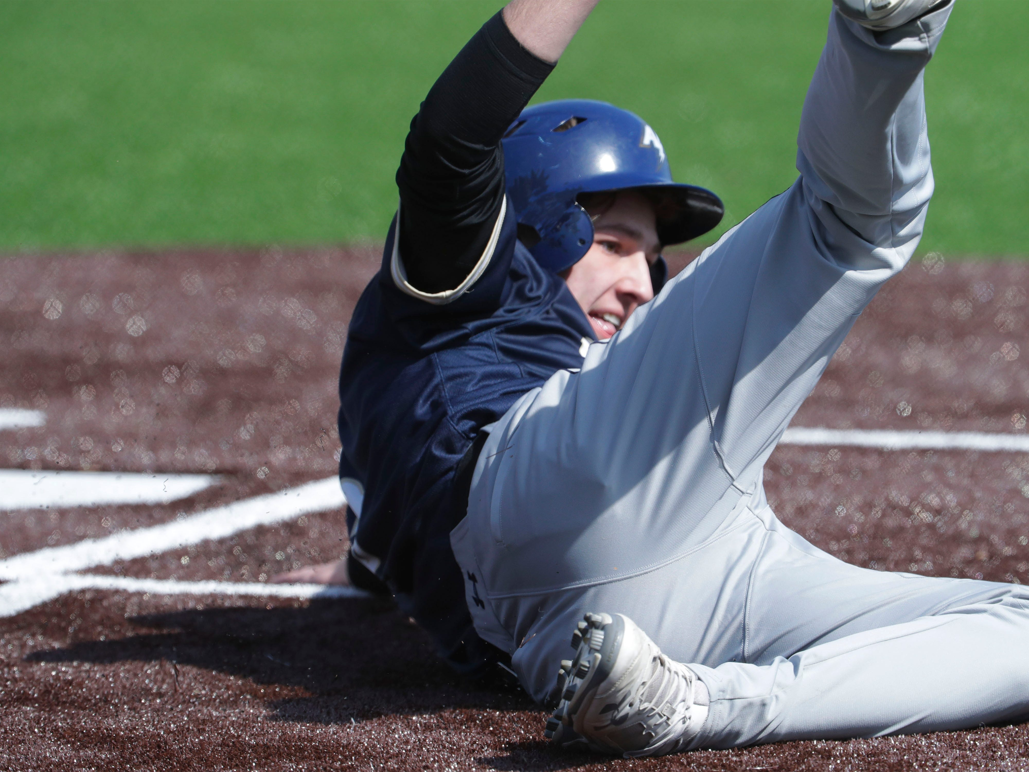Appleton North's Max Martine (5) slides into home during action with Sheboygan North, Friday, March 29, 2019, at the Field of Dreams complex in Sheboygan, Wis.