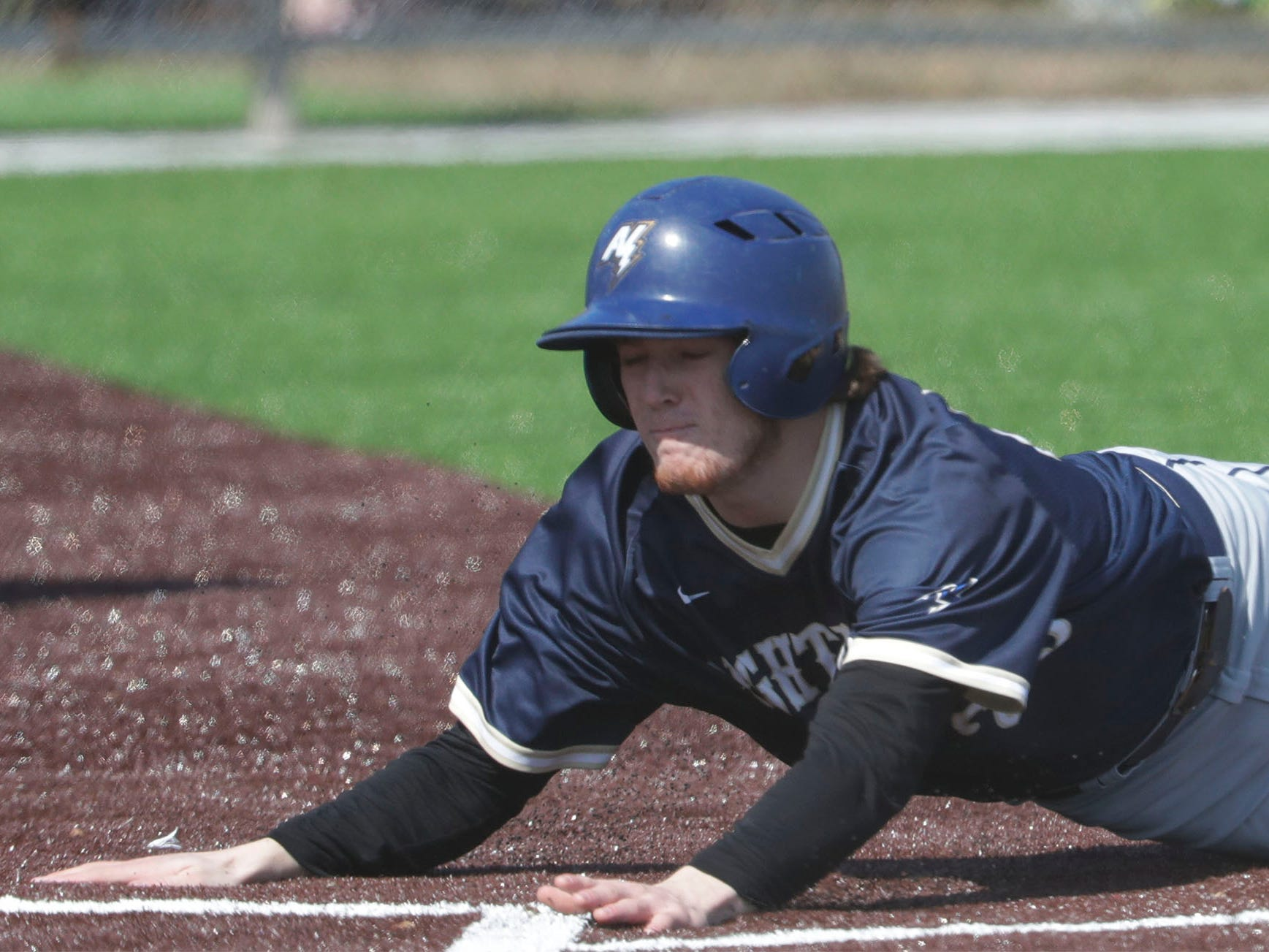 Appleton North's Aaron Reiland (25) slides into home, Friday, March 29, 2019, at the Field of Dreams complex in Sheboygan, Wis.